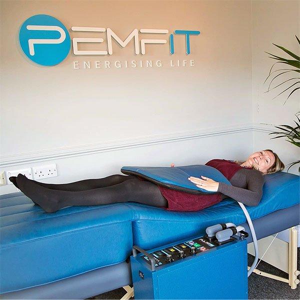 Woman Lying On PEMF Bed Using A Pad At PEMFiT